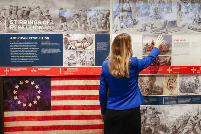 A staff member browses a display during a limited media availability at the National Veterans Museum and Memorial, Monday, Oct. 15, 2018, in Columbus, Ohio. A sweeping new museum in America's heartland honors the unifying experiences of U.S. military veterans outside the traditional trappings of military museums and war memorials. The 50,000-square-foot museum, which opens Oct. 27 in Columbus, Ohio, aims to honor, inspire, connect and educate with unique interactive experiences. (AP Photo/John Minchillo)