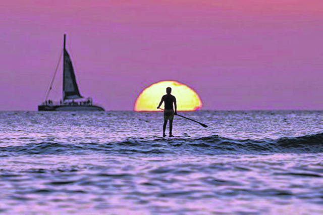 A paddleboarder looks our over the Pacific Ocean as the sun sets off of Waikiki Beach, in Honolulu, in 2013. When you're just starting out, even a weeklong vacation might seem like a one-way ticket to credit card debt — especially if you have a modest income or lack access to paid time off. But with the right moves, you can budget for travel without going into the red.