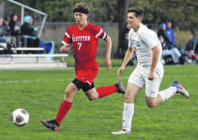 Allen East's Landon Gossard pursues Bluffton's Luke Young during Thursday night's Northwest Conference match at Bluffton.