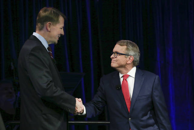 Democratic gubernatorial candidate Richard Cordray, left, and Ohio Attorney General and Republican gubernatorial candidate Mike DeWine shake hands before a debate at Cleveland State University, Monday, Oct. 8, 2018, in Cleveland. Rep. Mike DeWine and opponent Democrat Richard Cordray are locked in a close, expensive race to replace Republican Gov. John Kasich, who's term-limited. (David Petkiewicz/Cleveland.com via AP, Pool)