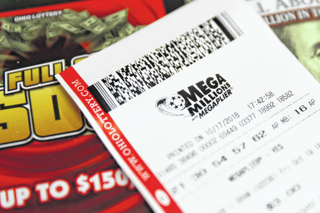 A Mega Millions lottery ticket rests on the shop counter at the Street Corner Market, Wednesday, Oct. 17, 2018, in Cincinnati. The estimated jackpot for Friday's drawing would be the second-largest lottery prize in U.S. history with a jackpot estimated to exceed $900 million.