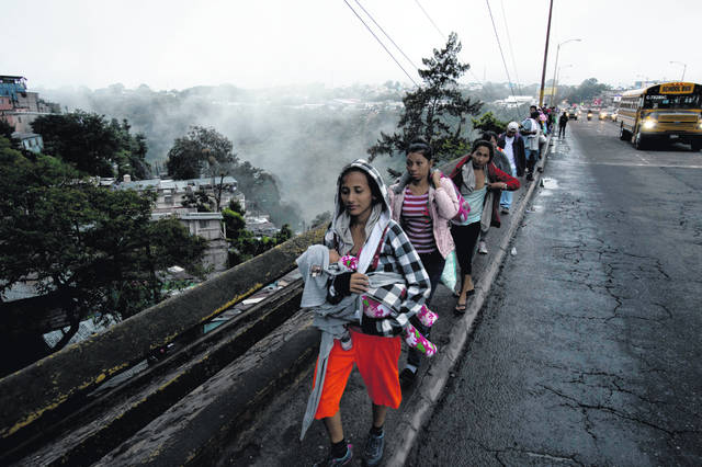 Honduran migrants leave Guatemala City at sunrise Thursday, Oct. 18, 2018 as they make continue their way north toward the U.S. Many of the more than 2,000 Hondurans in a migrant caravan trying to wend its way to the United States left spontaneously with little more than the clothes on their backs and what they could quickly throw into backpacks.