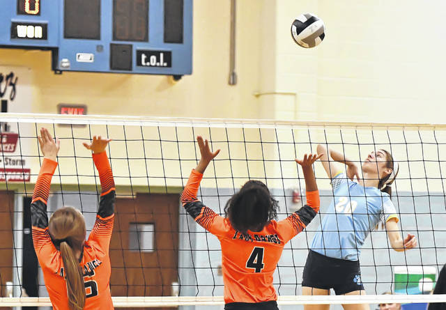 Elida's Hailey Little, left, and Amira Freeman go up to defend against Bath's Kaleigh Ketcham during Tuesday night's Division II match at Bath High School.