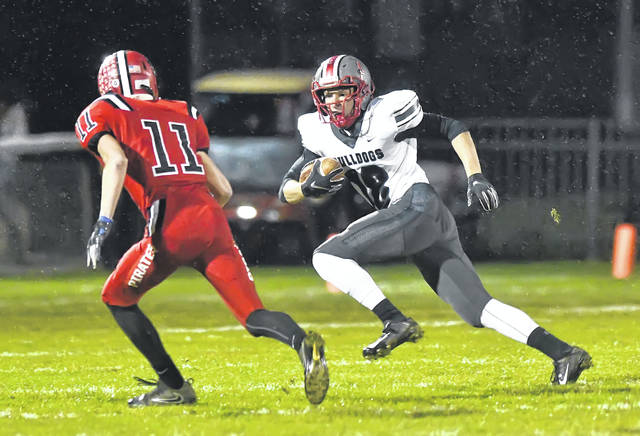 Columbus Grove's Adam Bogart looks to get past Bluffton's Tyson Shutler during Friday night's Northwest Conference game at Harmon Field in Bluffton. The Bulldogs share the Northwest Conference title with Crestview and Spencerville after the win.