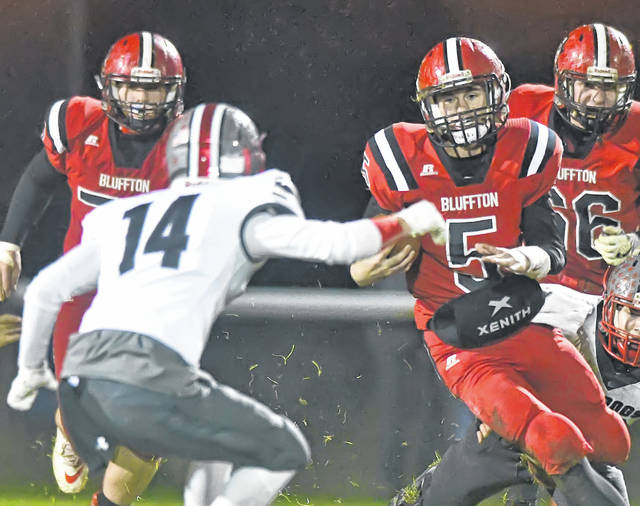 Bluffton's Nate Schaadt scrambles for yardagae against Columbus Grove's Trevor Taylor during Friday night's Northwest Conference game at Harmon Field in Bluffton.