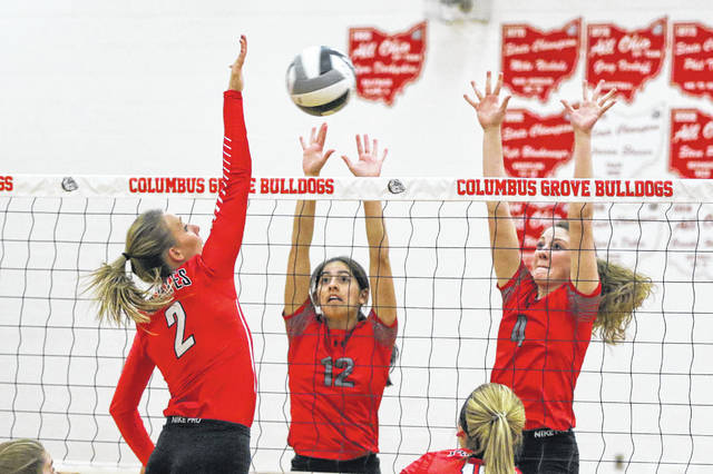 Columbus Grove's Becca Choi (12) and Cassie Heilman go up to defend against Bluffton's Ashley Eachus during Tuesday night's Division IV match at Columbus Grove. See more volleyball photos at LimaScores.com.