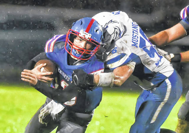 Crestview's Drew Kline fights for yardage against Allen East's Jonah Meyer during Friday night's Northwest Conference game at Crestview. Kline, the Knights' quarterback, turned to the read-option play and led the offense with 25 carries for 206 yards and two TDs.