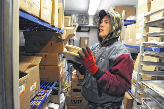 David Bradley, of Lima, restocks and rotates food items inside the walk-in cooler at Bob Evans Restaurant on Harding Highway in Lima.
