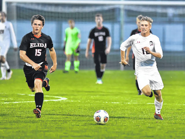 Shawnee's Jake Miller dribbles ahead of Elida's Joe Davis during Monday's match at the Elida Sports Complex.