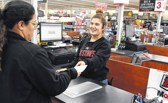 Kalen Myers, a cashier at Big R in Lima, hands a sales receipt to a customer. The store hopes to hire 10 or more employees for the holiday season. Employee incentives include a 20 percent discount off of store merchandise, a flexible schedule and potential Christmas bonuses. There is also potential for seasonal employees to become full-time once the holiday season is over.