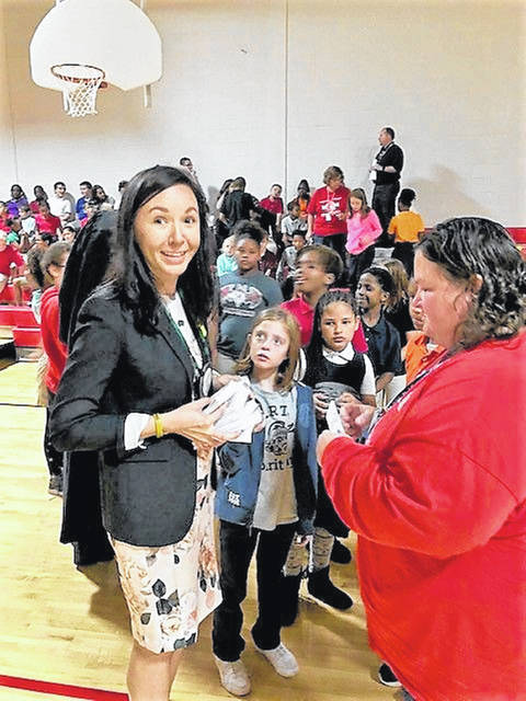 Optimist Club member Stephanie Moos hands out books to fourth-graders at Heritage Elementary as part of the Constitution Project.