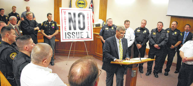 Police officers from all law enforcement agencies in Allen County surround Prosecuting Attorney Juergen Waldick during a press conference Thursday in opposition to state Issue 1, a proposed amendment to the Ohio constitution that will be decided by voters across the Buckeye State on Nov. 6.
