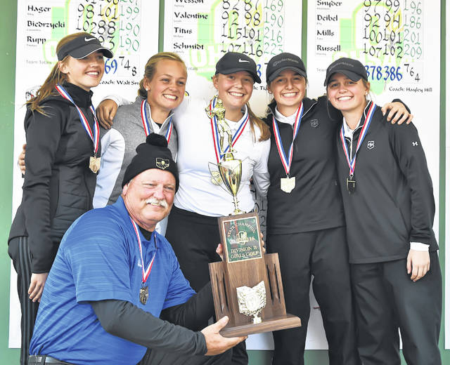 Lima Central Catholic Coach Daniel Reinicke holds the Division II girls golf state championship trophy won by, from left, Emma Mayers, Meghan Mulcahy, Hannah Garver, Erin Mulcahy and Mary Kelly Mulcahy on the Ohio State University Golf Club's Gray Course.
