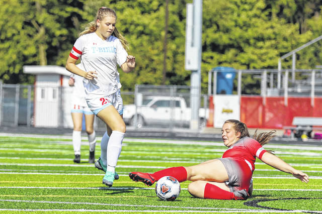 Lima Senior's Morgan Twining slides to get the ball away from Lima Central Catholic's Jessica Wilker during Saturday's match at Spartan Stadium.