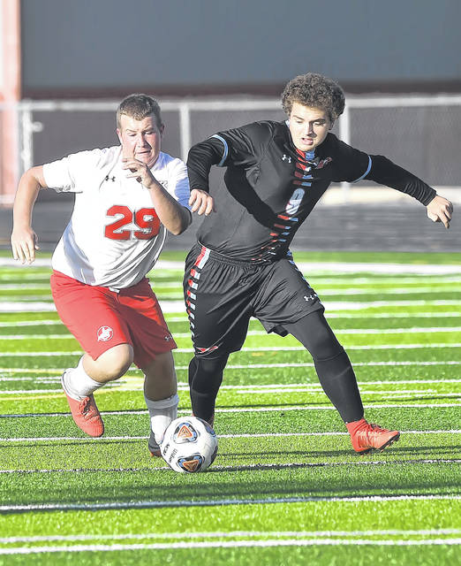 Lima Central Catholic's Brayden Truex, right, and New Knoxville's Carter Piehl compete for the ball during Wednesday's Division III sectional final match at Spartan Stadium.