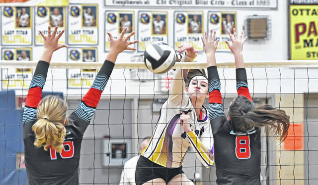 Leipsic's Hayley Heitmeyer hits a spike against Lima Central Catholic's Kennedy Parker, left, and Hannah Riepenhoff during Thursday night's Division IV district final at Ottawa-Glandorf's Robert J. Hermiller Gymnasium. See more volleyball photos at LimaScores.com.