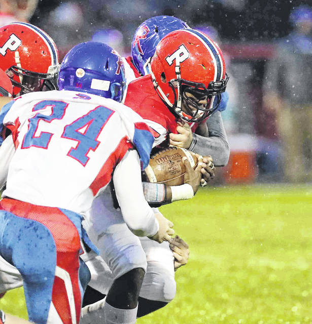 Perry's Nylan Cannon battles for yardage against Riverside's Brandon Sacks (24) during Friday night's Northwest Central Conference game at Perry. Cannon finished with 17 carries for 95 yards.