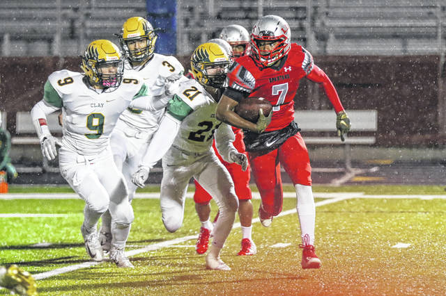 Lima Senior's Rashad Wallace scrambles from the Oregon Clay defense led by Caleb Meinke (21) during Friday night's Three Rivers Athletic Conference game at Spartan Stadium.