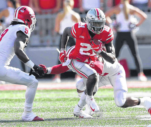Ohio State's Paris Campbell Jr. heads up field after making a catch against Indiana's Jonathan Crawford (9) and Marcelino Ball (right) during Saturday's game at Ohio Stadium in Columbus.