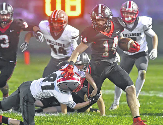 Columbus Grove's Rece Verhoff tries to bring down Spencerville's Cannan Johnson during Friday night's Northwest Conference game at Memorial Field in Spencerville. Johnson rushed for 105 yards on 23 carries with a TD in the victory, which sets up a four-way tie for first place in the Northwest Conference.