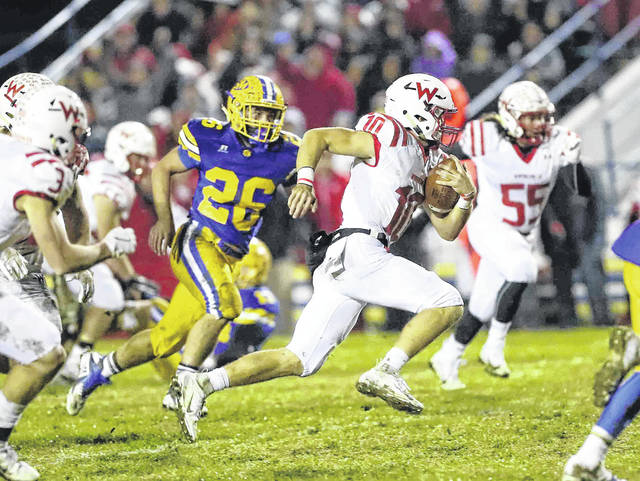 Wapakoneta's Brady Erb takes off up field in the first quarter, as St.Marys' Ty Schlosser is in pursuit in St. Marys on Friday. Erb finished the game with 149 yards passing and 160 yards on the ground for Wapakoneta, which won a share of the Western Buckeye League championship with the win.