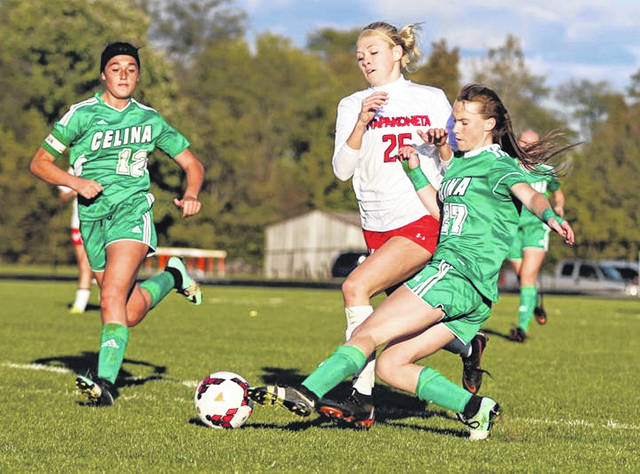 Celina's Mia Rolfes slides in to get the ball away from Wapakoneta's Morgan Follin as Celina's Alexa Billger (12) arrives during a Tuesday night Division II district semifinal at Elida. See more soccer photos at LimaScores.com.