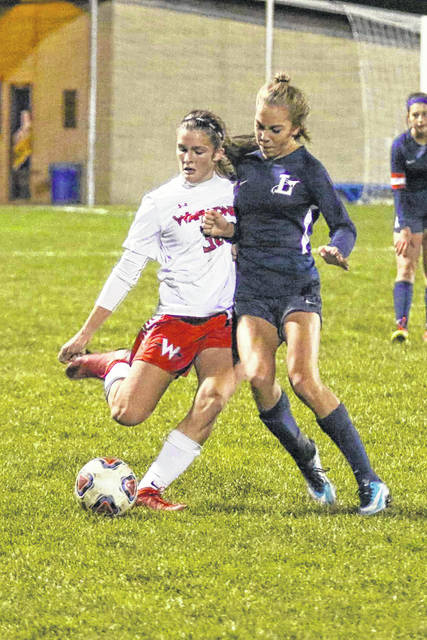 Lake's Ava Ayers attempts to knock Wapakoneta's Hayden Lawrence off the ball as she clears it down the field during the Division II Regional Semi-Final on Tuesday evening at Findlay High School.