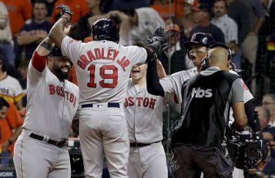 Boston Red Sox's Jackie Bradley Jr. celebrates with teammate after hitting a grand slam against the Astros during the eighth inning in Game 3 of the American League Championship Series in Houston. (AP Photo)