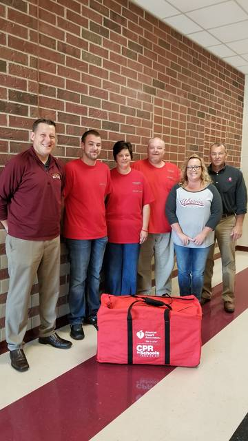 Marcus Landin's brother, Kyle, and parents, Melinda and John, present a CPR instruction kit to Kalida High School Principal Dean Brinkman, teacher Darla Warnecke and Superintendent Karl Lammers.