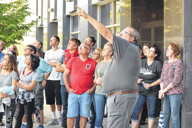 Bob Cook points to a nearby building as he spins tales about some of the haunted happenings that occured in downtown Lima.