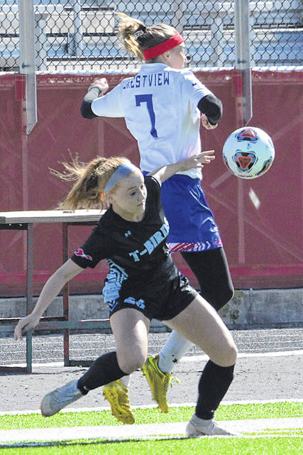 Lima Central Catholic's Annika Welker battles Crestview's Hope Loyer for the ball during Saturday's Division III tournament match at Spartan Stadium.