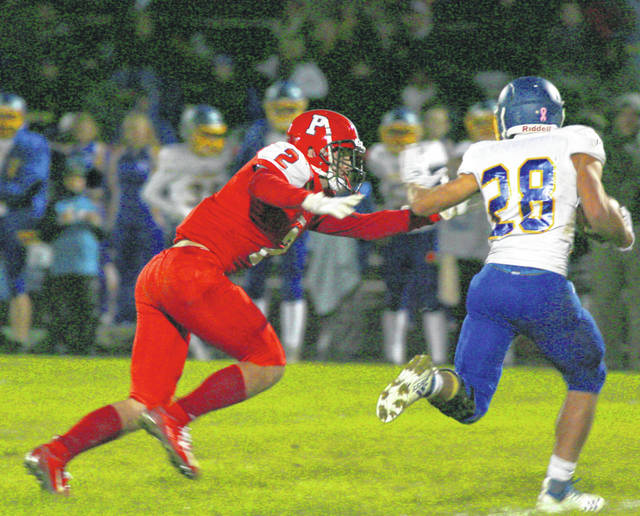 Perry's Shane Overly closes in on Lehman Catholic running back Tyler Sollman during Friday night's Northwest Central Conference game at Perry.