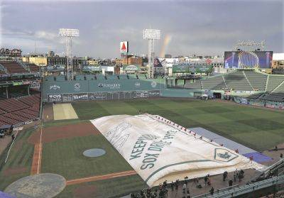 Groundskeepers remove the tarp over the Fenway Park infield following a rain storm Tuesday before Game 1 of the World Series between the Red Sox and Los Angeles Dodgers in Boston.