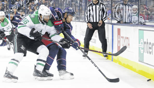 Dallas' Gemel Smith, left, and the Blue Jackets' Markus Hannikainen chase a loose puck during Tuesday night's game in Columbus.