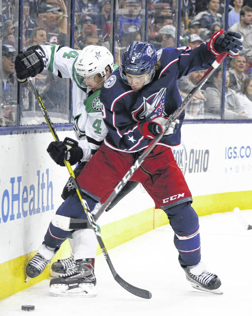 Dallas' Miro Heiskanen, left, and the Blue Jackets' Artemi Panarin fight for a loose puck during Tuesday night's game in Columbus.