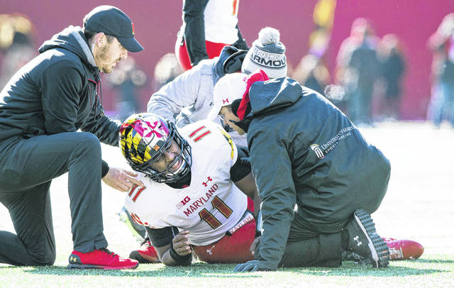 Team trainers examine Maryland quarterback Kasim Hill during Saturday's game against Indiana, in Bloomington, Ind.