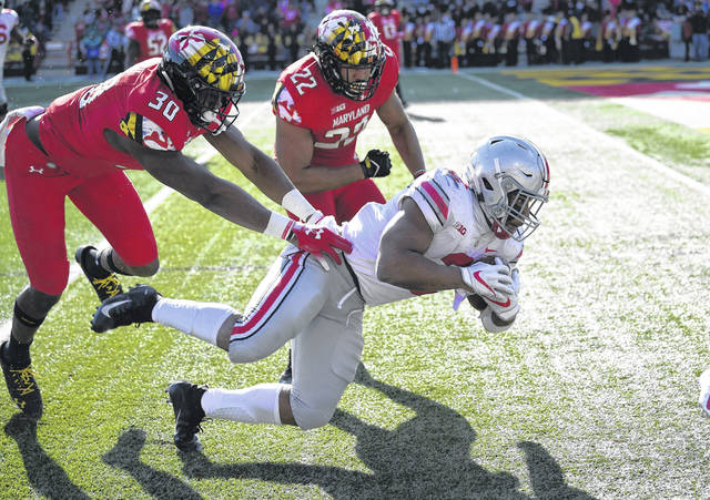 Ohio State's J.K. Dobbins dives for yardage against Maryland's Isaiah Davis (22) and Durell Nchami (30) during Saturday's Big Ten game in College Park, Md.