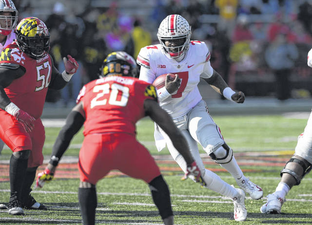 Ohio State's Dwayne Haskins Jr. (7) looks for an avenue past Maryland's Antwaine Richardson (20) and Oluwaseun Oluwatimi (52) during Saturday's Big Ten game in College Park, Md.