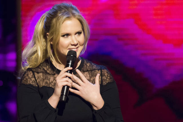 FILE - In this Saturday, Feb. 28, 2015 file photo, Amy Schumer appears onstage at the Beacon Theatre in New York. On Friday The Associated Press has found that a photo circulating on the internet showing Schumer splattered with blood and tearing a doll apart was doctored. The photo is paired with a quote falsely attributed to her about fetuses and abortion.