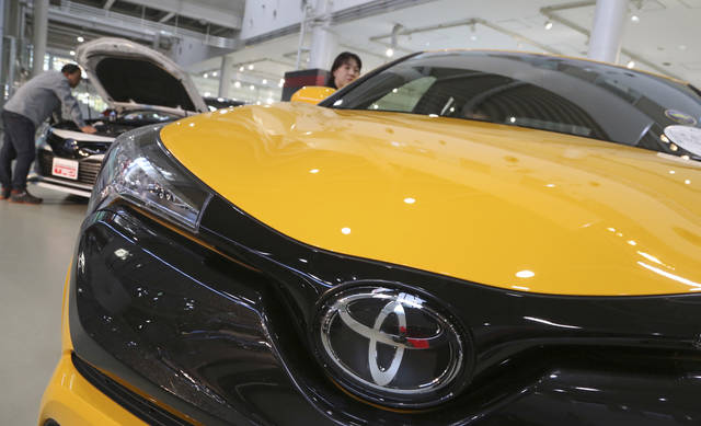 In this Nov. 13, 2017, photo, visitors take a look at Toyota cars at the automaker's showroom in Tokyo. Toyota Motor Corp. has raised its earnings forecast after reporting that its profit surged 28 percent in the last quarter on growing sales and cost cuts. The top Japanese automaker said Tuesday, Nov. 6, 2018, that its July-September profit was 585.1 billion yen ($5.2 billion), up from 458.3 billion yen the year before (AP Photo/Koji Sasahara)