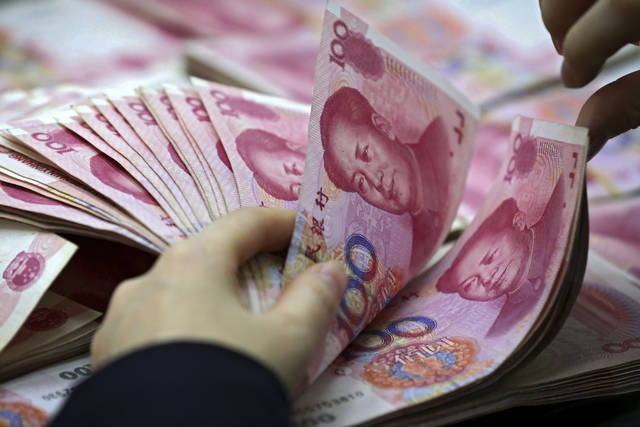 FILE - In this Nov. 25, 2016, file photo, a clerk counts Chinese currency notes at a bank outlet in Huaibei in central China's Anhui province.  China's foreign currency reserves declined in October, 2018, suggesting Beijing might be intervening in market to keep its yuan's politically sensitive exchange rate from falling to far against the dollar. Central bank data on Wednesday, Nov. 7, 2018, showed the reserves, the world's biggest, contracted by about $34 billion to just over $3 trillion.(Chinatopix via AP, File)