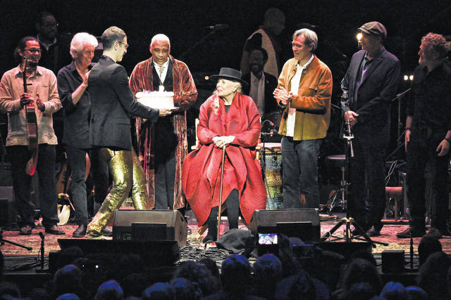 "Joni Mitchell is presented with a birthday cake on stage at ""JONI 75: A Birthday Celebration"" on Wednesday at the Dorothy Chandler Pavilion in Los Angeles."