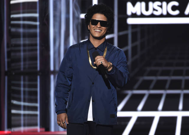 "FILE - In this May 20, 2018, file photo, Bruno Mars presents the Icon award at the Billboard Music Awards at the MGM Grand Garden Arena in Las Vegas. Mars will mark the end of his massive ""24K Magic World Tour"" by providing meals to 24,000 Hawaii residents in need for the Thanksgiving holiday. The singer, who was born and raised in Honolulu, Hawaii, announced Sunday, Nov. 11, he has donated money to the Salvation Army's Hawaiian and Pacific Islands Division, which holds an annual Thanksgiving meal program to help those in need. (Photo by Chris Pizzello/Invision/AP, File)"