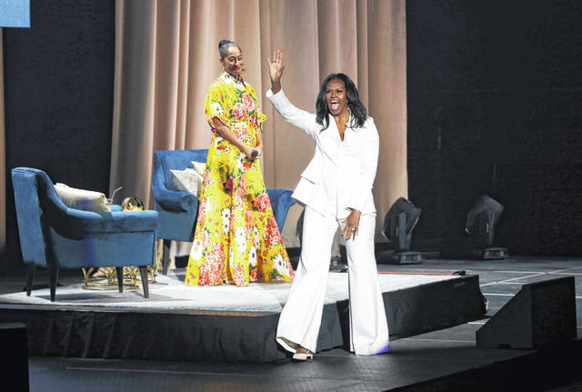 "Former first lady Michelle Obama greets the audience as Tracee Ellis Ross watches at the ""Becoming: An Intimate Conversation with Michelle Obama"" event at the Forum on Thursday in Inglewood, Calif."