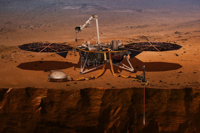 FILE - This illustration made available by NASA in 2018 shows the InSight lander drilling into the surface of Mars. InSight, short for Interior Exploration using Seismic Investigations, Geodesy and Heat Transport, is scheduled to arrive at the planet on Monday, Nov. 26, 2018. (NASA via AP)