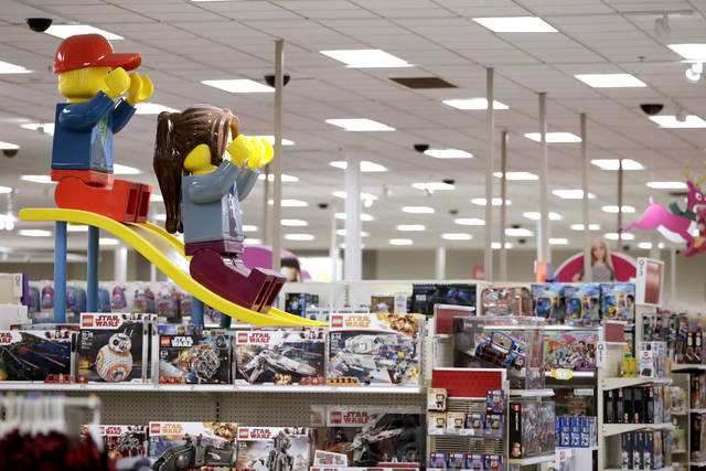In this Friday, Nov. 16, 2018, photo a display shows two large Lego toys on a slide near the toy section at a Target store in Bridgewater, N.J. Companies from Target to online mattress company Casper aren't just counting on a stronger economy to pump up sales. Target's CEO Brian Cornell estimated last month there's up to $100 billion in market share for grabs, double what he foresaw just a year ago. So Target is accelerating its store remodels in areas where bankrupt retailers had stores. (AP Photo/Julio Cortez)