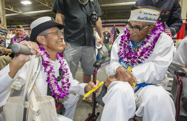 FILE - In this Dec. 7, 2016, file photo, Kathleen Chavez, left, talks with her father Ray Chavez, right, age 104, of the USS Condor, the oldest living survivor from the Pearl Harbor attacks along with the remaining living survivors of the USS Arizona gathered at the World War II Valor in the Pacific National Monument at Joint Base Pearl Harbor-Hickam in Honolulu. Ray Chavez, the oldest U.S. military survivor of the Dec. 7, 1941, attack on Pearl Harbor that plunged the United States into World War II has died at age 106. Chavez's daughter, Kathleen Chavez of Poway, Calif., tells The Associated Press her father died in his sleep Wednesday, Nov. 21, 2018. (AP Photo/Eugene Tanner, File)