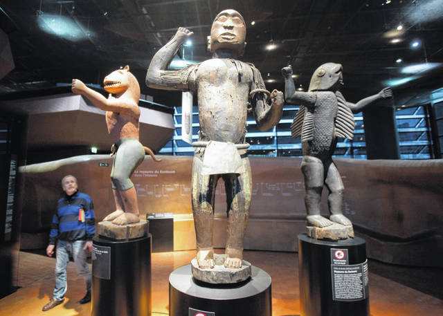 Visitors look at wooden royal statues of the Dahomey kingdom, dated 19th century, today's Benin, at Quai Branly museum in Paris, France, on Friday. From Senegal to Ethiopia, artists, governments and museums are eagerly awaited a report commissioned by French President Emmanuel Macron on how former colonizers can return African art to Africa.
