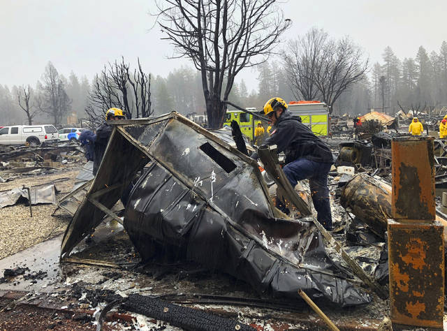 Steven McKnight, right, and Daniel Hansen saw through large pieces of sheet metal so they can be moved to allow cadaver dogs to search beneath them for signs of human remains at a mobile home park in Paradise, Calif., Friday, Nov. 23, 2018. They said the mobile home park had already been hand searched, so they were re-examining it with search dogs. (AP Photo/Kathleen Ronayne)