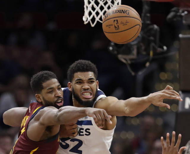 Cleveland Cavaliers' Tristan Thompson, left, and Minnesota Timberwolves' Karl-Anthony Towns battle for a loose ball in the second half of an NBA basketball game, Monday, Nov. 26, 2018, in Cleveland. The Timberwolves won 102-95. (AP Photo/Tony Dejak)